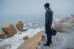 Ein hübscher junger Mann untersucht den Abstand auf den Felsen Lizenzfreie Stockfotografie