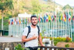 Ein hübscher Kerl mit einem Bart raucht eine elektronische Zigarette auf dem Hintergrund von Bergen und von Flaggen von unterschi Stockfotografie