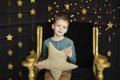 Ein hübscher kleiner Junge sitzt in einem Stuhl, der ein sternförmiges Kissen in einem Innenraum mit goldenen Sternen auf einem S stockfotos