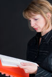 Ein hübscher weiblicher Managermesswert durch ein Faltblatt mit einem schwarzen Ba Lizenzfreies Stockbild
