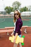 Ein hübsches blondes Mädchen, das kariertes Hemd, weiße Kappe und Sonnenbrille trägt, steht auf dem Sportfeld mit einem Gelb lizenzfreies stockbild