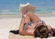 Ein hübsches Mädchen breitet auf dem Strand aus Stockbild