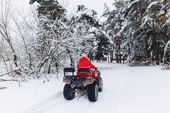 Ein hübsches Mädchen, das ein quadrocycle in einem malerischen schneebedeckten Bereich reitet stockfotos