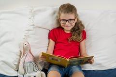 Ein hübsches Mädchen mit Gläsern, eine Grundschülerlesung Stockfotografie