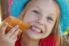 Ein hübsches Mädchen mit 5-Jährigen mit Hut isst ein Brötchen Lizenzfreie Stockfotos