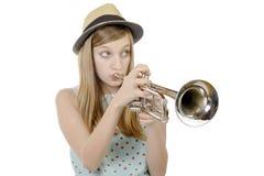 Ein hübsches Mädchen spielt Trompete lizenzfreie stockfotos