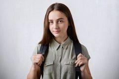 Ein hübsches Schulmädchen mit dem langen geraden Haar und dunklen schönen den Augen, die das elegante Hemd hält Rucksack auf ihre Stockbilder