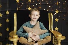 Ein h?bscher kleiner Junge sitzt in einem Stuhl, der ein sternf?rmiges Kissen in einem Innenraum mit goldenen Sternen auf einem S stockbilder