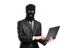 Ein Hacker, der an einem Laptop arbeitet Stockbild
