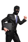 Ein Hacker in der Raubschablone, die mit Laptop läuft Stockfoto