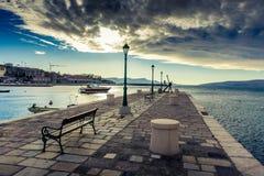Ein Hafen mit einem Boot von a und einem Pier mit Lampen und einem grauen stürmischen Himmel lizenzfreies stockbild