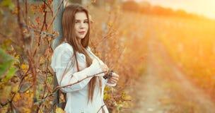 Ein halb nacktes Brunettemädchen in einer weißen Weinlesebluse und in einem langen Haar, die vor dem hintergrund eines Herbstwein Stockfoto