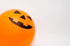 Ein Halloween-Steckfassung-Olaternengesicht auf einem orange Ballon auf weißem Hintergrund lizenzfreies stockbild