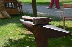 Ein Hammer, der auf einen Amboss im Park am sonnigen Tag legt lizenzfreies stockfoto