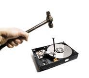 Ein Hammer schlägt einen Nagel in das Festplattenlaufwerk vom Computer Lizenzfreies Stockfoto