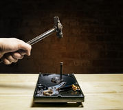 Ein Hammer schlägt einen Nagel in das Festplattenlaufwerk vom Computer Lizenzfreies Stockbild