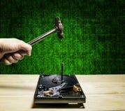 Ein Hammer schlägt einen Nagel in das Festplattenlaufwerk vom Computer im Th Stockfoto