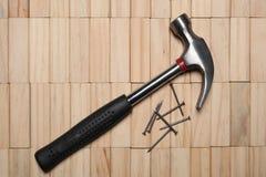 Ein Hammer und einige Nägel stehen auf einer Holzklotzpflasterung mit Kopienraum still stockfoto