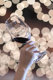 Ein Hand ein Weinglas an einer Partei, Hintergrund mit unscharfen Lichtern Stockbild