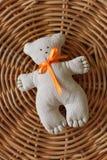 Ein handgemachter Teddybär mit einem orange Band auf einer Strohmatte Spielwaren für Babys Stockfoto
