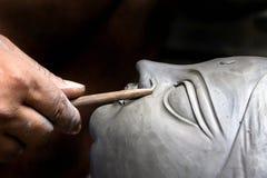 Ein Handwerker, der Kopf des Lehmidols erstellt Lizenzfreie Stockfotografie