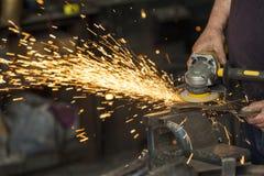 Ein Handwerker, der mit einem Hammer und einem Ambosse arbeitet Stockbild