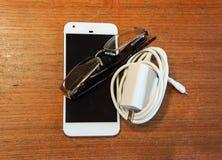 Ein Handy mit einem Ladegerät und ein Paar von Ablesenglassese Lizenzfreie Stockfotografie