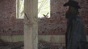 Ein harter Junge in einem schwarzen Regenmantel geht durch einen verlassenen Hangar Die Kamera folgt ihm stock footage