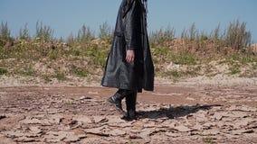 Ein harter Junge in einem schwarzen Regenmantel und in einem Hut läuft die Wüste durch Er sieht wie ein Verfolger aus stock video