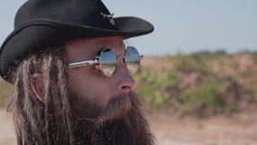 Ein harter Junge mit einem Bart und dunklen Gläsern geht in die Wüste Nahaufnahme seines Gesichtes stock footage