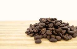 Ein Haufen von Kaffeebohnen auf einem hölzernen Brett Stockbild