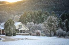 Ein Haus auf einem schneebedeckten Hügel Stockbild