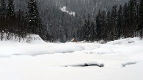 Ein Haus in den Bergen auf dem Ufer von einem schneebedeckten Fluss stock footage