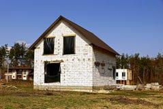 Ein Haus gebaut vom weißen Ziegelstein mit einem Schwarzen celofan auf den Fenstern Stockfoto