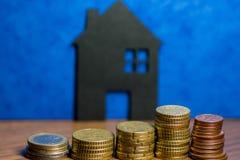 Ein Haus gemacht von der Tafel und ein Stapel Euromünzen in einem blauen b Lizenzfreies Stockfoto