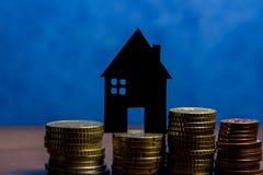 Ein Haus gemacht von der Tafel und ein Stapel Euromünzen in einem blauen b Stockfotografie