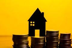 Ein Haus gemacht von der Tafel und ein Stapel Euromünzen in einem Gelb Stockfotos
