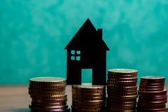 Ein Haus gemacht von der Tafel und ein Stapel Euromünzen in einem Grün Lizenzfreie Stockfotografie