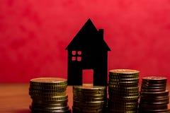 Ein Haus gemacht von der Tafel und ein Stapel Euromünzen in einem roten Ba Lizenzfreie Stockbilder