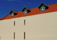 Ein Haus mit rotem Ziegeldach und drei Mansarden Stockbild