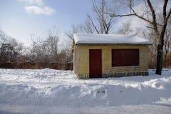 Ein Haus mit roter Tür auf dem Schneegebiet Lizenzfreie Stockfotos