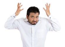 Ein hübscher junger Mann, der eine schlechte Haltung und ein Temperament anheben seins hat, teilt in der Luft als ob aus, um zu sa Lizenzfreie Stockfotografie