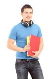 Ein hübscher Student mit den Kopfhörern, die Bücher halten Stockfotografie