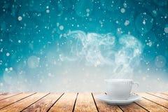 Ein heißer Kaffee auf dem Tisch auf einem Winterhintergrund stockbild