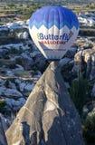 Ein Heißluftballon fliegt hinter einen feenhaften Kamin bei Sonnenaufgang nahe Goreme in der Cappadocia-Region von der Türkei Lizenzfreie Stockfotografie