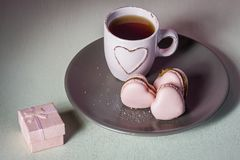 Ein Heiratantrag Heiraten Sie mich? Rosa Herz macarons mit hellrosa Teeschale auf dem Platten- und Cremehintergrund lizenzfreie stockbilder