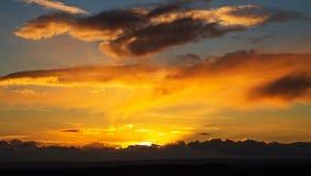 Ein heller Sonnenuntergang gegen einen bewölkten Himmel Stockbilder