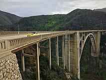 Ein helles gelbes Chevrolet Camaro beschleunigt über die Bixby-Nebenfluss-Brücke, Big Sur, Kalifornien Lizenzfreie Stockfotos
