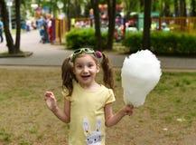 Ein helles Sommerfoto mit einem kleinen lachenden Mädchen, das Süßigkeitsbaumwolle hält Stockfoto