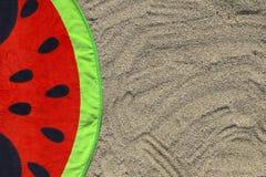 Ein helles Tuch mit einem Wassermelonendruck auf dem Sand Stockfotos